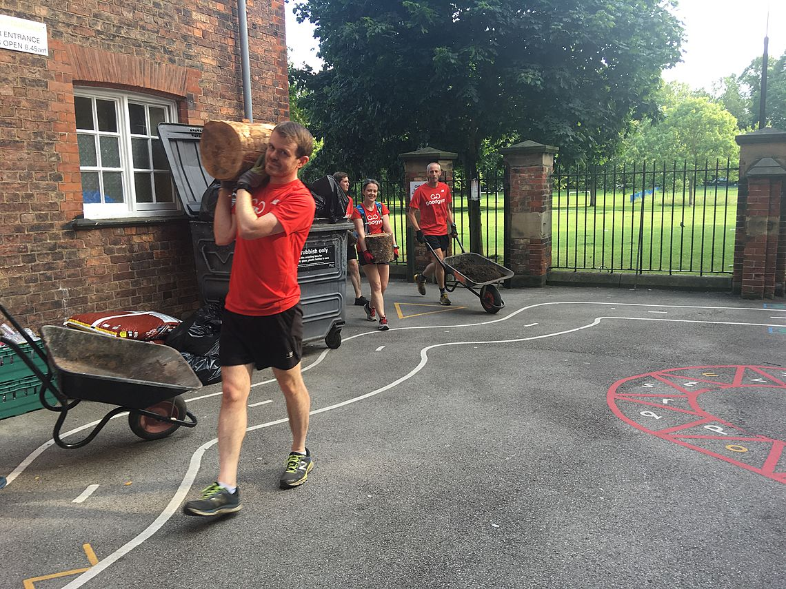 GoodGym members complete a task, carrying logs and wheelbarrows