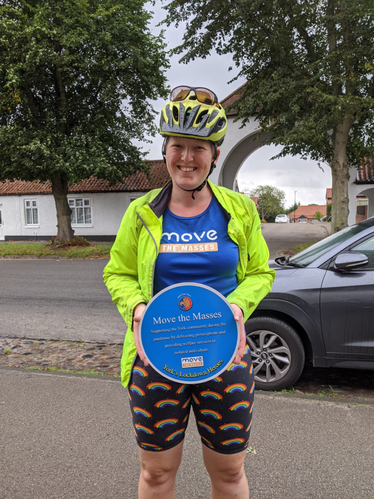 Debs holding plaque in cycling gear