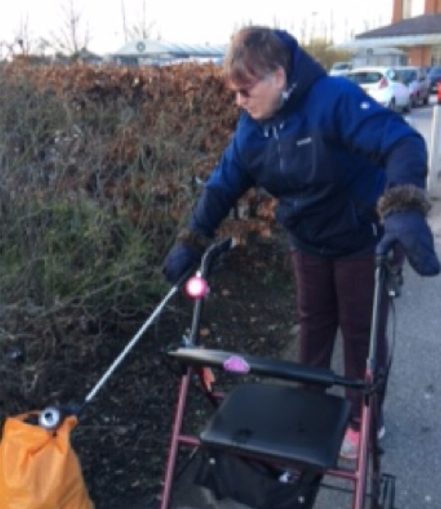A woman picking up litter while getting out as part of a Move Mates project.