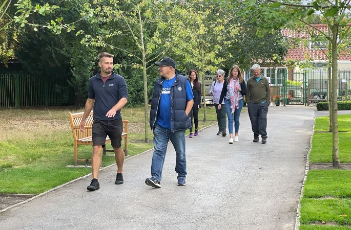A mixed group of people walking in a park