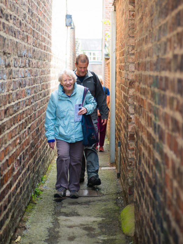 People walking in a brick alleyway